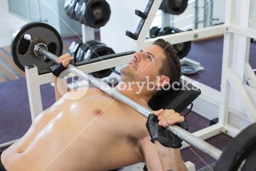 Shirtless bodybuilder lifting heavy barbell weight lying on bench
