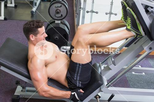 Shirtless bodybuilder working on his legs with weight machine