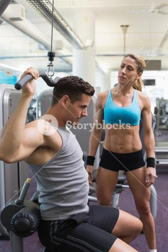 Bodybuilder using weight machine for arms with encouraging trainer