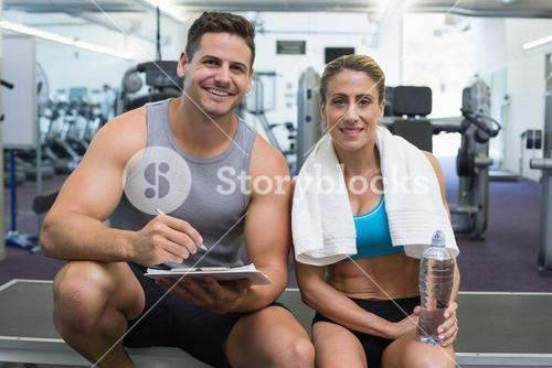 Female bodybuilder sitting with personal trainer smiling at camera