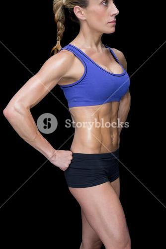 Strong woman posing in sports bra and shorts