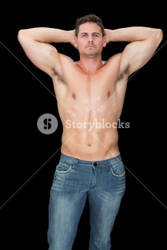 Handsome muscular man posing in blue jeans