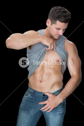 Muscular man lifting up his vest to show abs