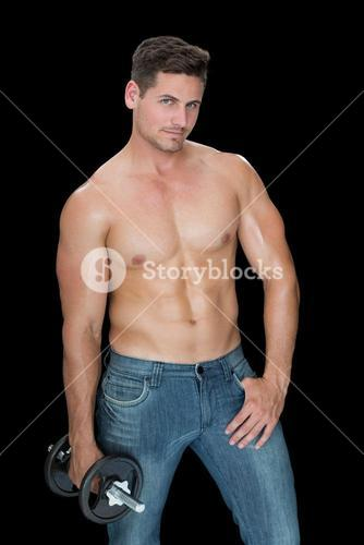Muscular man holding large dumbbell in blue jeans
