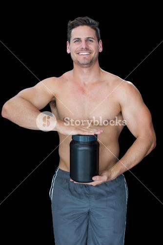 Muscular man posing with nutritional supplement
