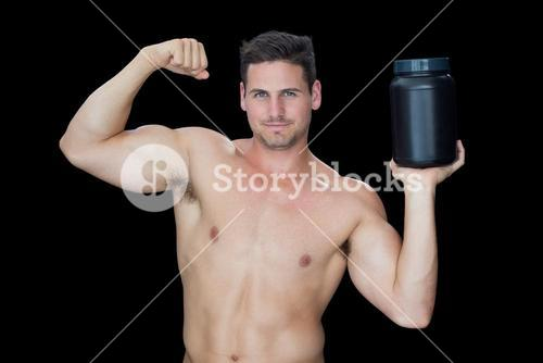Happy muscular man posing with nutritional supplement