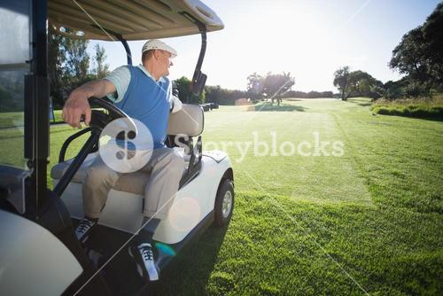 Golfer driving his golf buggy in reverse