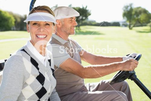 Happy golfing couple driving in their buggy
