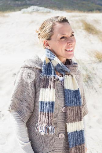 Attractive smiling blonde standing on the beach