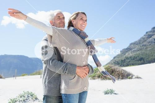 Carefree couple hugging on the beach in warm clothing