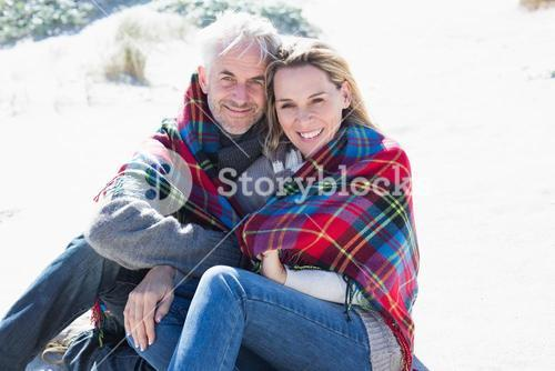 Happy couple wrapped up in blanket sitting on the beach