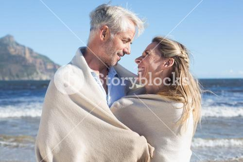 Smiling couple wrapped up in blanket on the beach