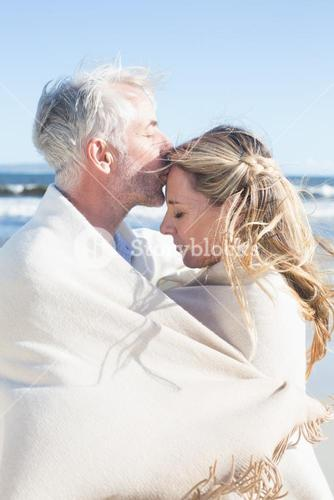 Affectionate couple wrapped up in blanket on the beach