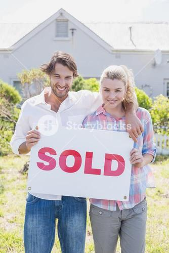 Happy couple smiling at camera holding sold sign