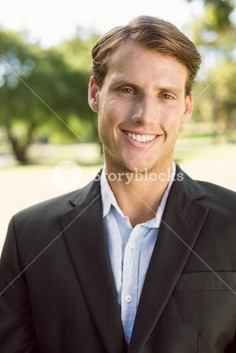 Handsome businessman in the park smiling at camera
