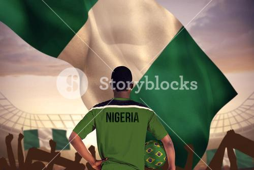 Composite image of nigeria football player holding ball