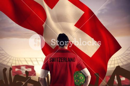 Composite image of swiss football player holding ball