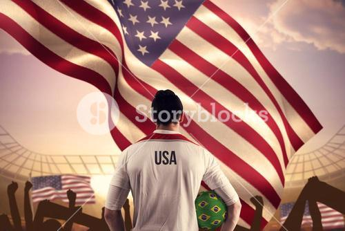 Composite image of usa football player holding ball