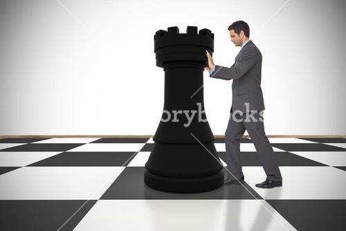 Composite image of businessman pushing chess piece