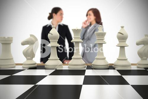 Composite image of businesswomen and chess pieces