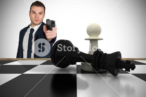 Composite image of serious businessman pointing a gun at chess piece