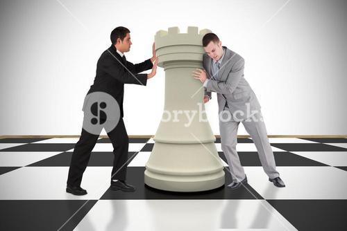 Composite image of business people pushing chess piece