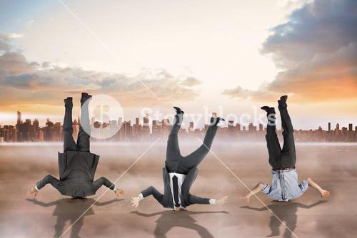 Composite image of businessmen burying their heads