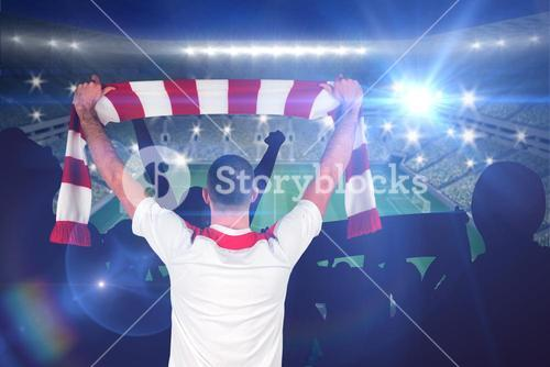 Composite image of football player holding striped scarf