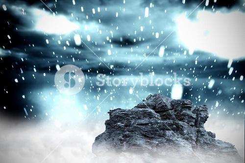Large rock overlooking snowy sky
