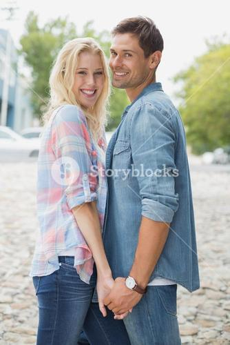 Hip young couple holding hands smiling at camera
