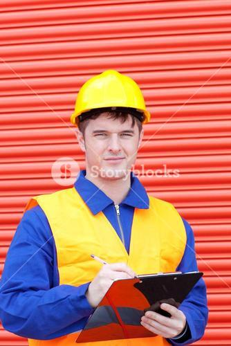Happy male engineer writing his report