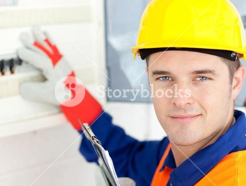 Smiling electrician repairing a power plan