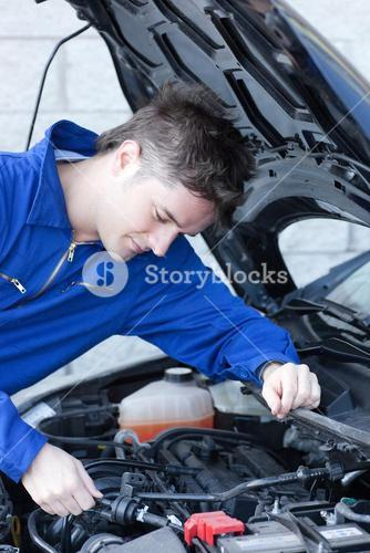 Concentrated man repairing a car