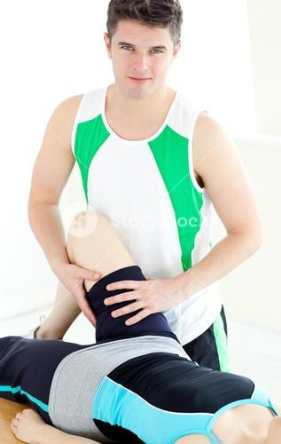 Attractive male physical therapist checking a womans leg