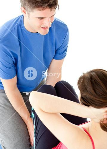 Brunette woman doing situps assited by her personal trainer