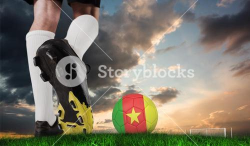 Composite image of football boot kicking cameroon ball