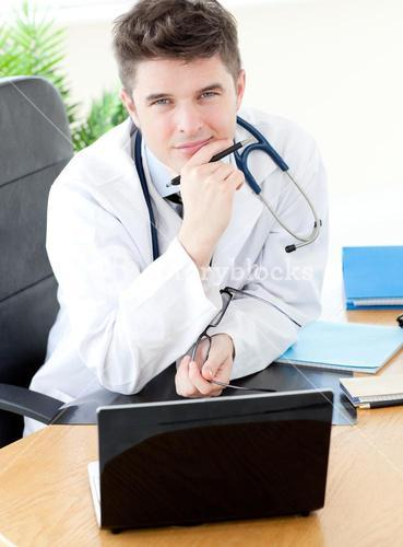 Smiling male doctor using a laptop sitting at his desk