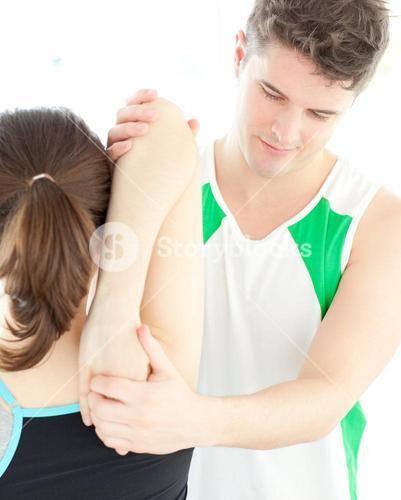 Young physical therapist checking a womans shoulder