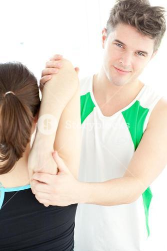 Smiling physical therapist checking a womans shoulder