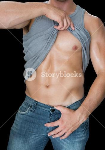 Muscular man lifting his tank top in blue jeans