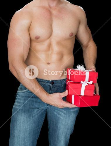 Muscular man holding pile of presents in blue jeans