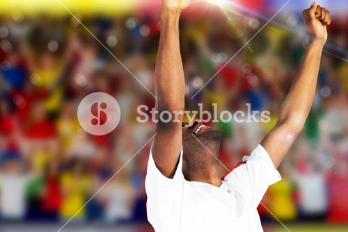Composite image of excited handsome football fan cheering