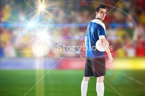 Composite image of handsome football player in blue jersey