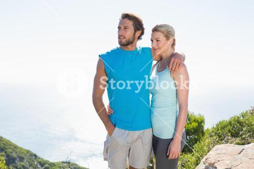 Fit couple standing at summit