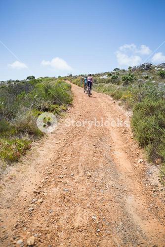 Fit couple cycling up mountain trail