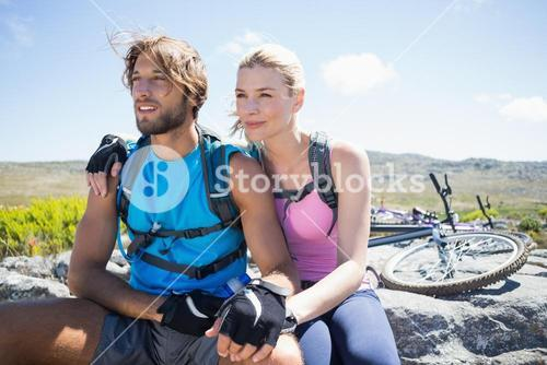 Fit cyclist couple taking a break on rocky peak