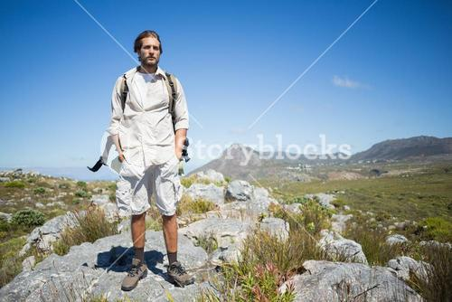 Handsome hiker standing at the summit