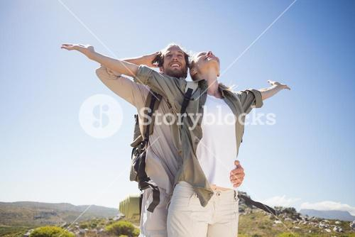Hiking couple standing on mountain terrain admiring the view