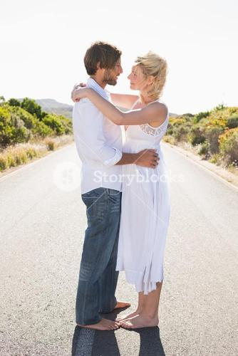 Attractive couple embracing barefoot on the road