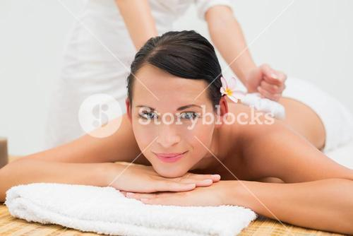 Peaceful brunette enjoying a herbal compress massage smiling at camera